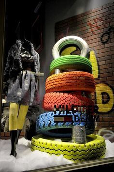 Good use of recycled elements in the window - old tires painted in bright colors Mais Window Display Retail, Christmas Window Display, Window Display Design, Denim Window Display, Visual Merchandising Displays, Visual Display, Vitrine Jean, Vitrine Design, Clothing Store Design