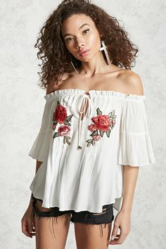A woven off-the-shoulder top featuring an elasticized neckline, self-tie front, an embroidered floral design on the front, short sleeves, and a curved hem.