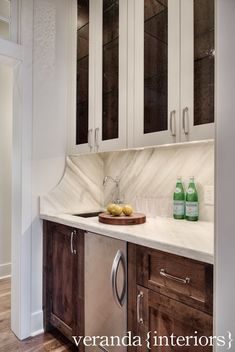 Built-in wet bar with white seeded glass front upper cabinets accented with glass shelves over a white leathered marble backsplash and countertop which frames a stainless steel bar sink with hook spout faucet over stained alder wood cabinets accented with polished nickel cabinet pulls on either side of a stainless steel beverage fridge.
