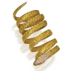 GOLD, DIAMOND AND COLORED STONE SNAKE BRACELET, LATE 19TH CENTURY The coiling serpent of braided gold decorated at the head with numerous rose-cut diamonds, completed by small round ruby eyes.