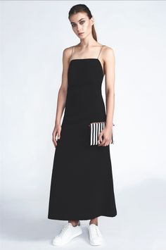 Open back, ankle lenght crepe fabric dress with four chain straps can be styled in multiple ways. Chain color is silver. Comes out of the black and white striped  C-ya Bag. Black