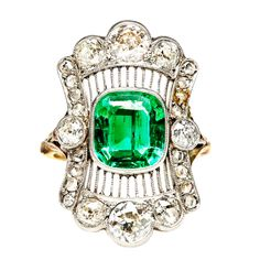 Intricately designed platinum and 18k yellow gold Edwardian era navette ring featuring a spectacular bezel set natural Colombian emerald. Two artfully curved rows of bead set single cut diamonds and platinum filigree work suspend six sparkling Old European cut diamonds to complete the dramatic scalloped frame of this exquisitely unique vintage ring, while two more Old European cut diamonds anchor the position of the stunning 18k gold band for a total of 3.0cts in total diamond weight. C…