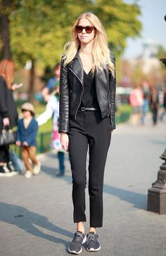 A fancy black top is worn with a leather jacket, belted trousers, and Nike sneakers