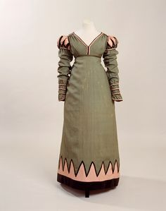 archery dress  Date: 1820-1825 Lincoln green plain weave mohair and worsted mixture, trimmed with salmon pink mohair / worsted mix and black velvet.