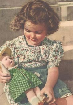 Sweet old postcard of a girl holding her dolly.