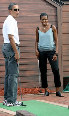 United States President Barack Obama and First Lady Michelle Obama watch as The President misses the hole while playing miniature golf