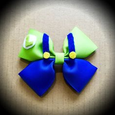 Super Mario Character Inspired Green Luigi Cartoon Hair Bow  Blue & Green Grosgrain Ribbon Decorated with Felt Accents.  Mounted on an alligator clip.  I can do custom bows, just let me know if youd like something specific.  Price is for single bow.