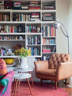 Estante recheada de livros + mesas de apoio com pés palito + poltrona com pés palito