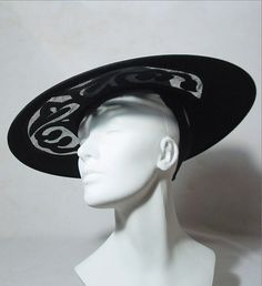 1940's cartwheel hat with peekaboo cutouts (front view) | Label: Martha Gene New York | Black felt wide circular brim, with almost flat crown. There are very alluring peekaboo cutouts in the front of the brim (interesting sort of S curve styling). These cut-outs are filled with net | The hat features a gross grain ribbon around the brim and ornamenting the back. It has a grosgrain ribbon with elastic to be worn under the hair and to the back