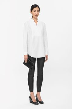 This cotton poplin shirt has a crossover textured panel along the front and cut-out collar, designed to look like inverted lapels. A long, straight shape, it has a curved hemline and neat button cuffs.