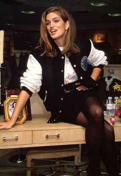 Cindy Crawford wearing varsity jacket and mini skirt in 1990