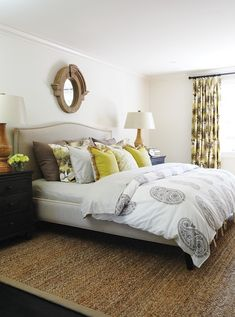 House & Home    beautiful yellow & brown bedroom design with soft white walls, Crate & Barrel Colette camel back Bed with nailhead trim, jute rug with gray trim, black nightstands chests, antique wood balusters and finials architectural salvage lamps, yellow & brown pillows, white duvet with gray paisley print, Restoration hardware Mansard mirror and yellow & brown floral drapes.