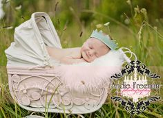 Newborn baby boy smiling in vintage white carriage wearing blue prince crown.  Outdoor newborn session.   www.TheAthensNewbornPhotographer.com