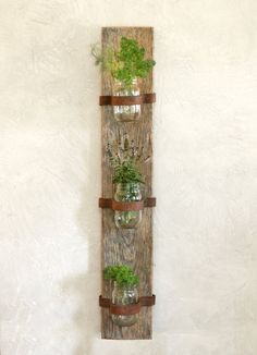 """This vertical garden features three mason jars. It's a perfect space saving herb garden that would be a rustic addition to any kitchen or patio. Fill it with fresh-cut flowers and hang it in the dining room. It also looks adorable as a bathroom organizer holding Q-tips and cotton balls. The leather straps can be tightened or loosened by twisting the screw.  SIZE The finished product is 36"""" tall x 6"""" wide x 5.5"""" deep.  HANGING All hardware needed for hanging is included. It's always best to…"""