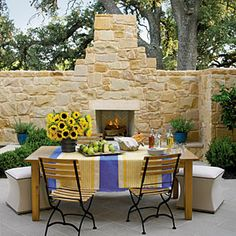 With the addition of a built-in fireplace, a privacy wall becomes a focal point of this outdoor living space. | SouthernLiving.com