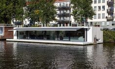 Dutch +31 Architects' new tranquil houseboat is moored in an Amsterdam River.