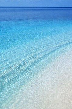 Crystal clear waters on a beach in Naxos. Click to shop swimwear by Matthew…