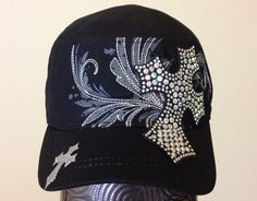 This black cadet cap features a charcoal grey screen printed pattern across the front of the hat, along with silver embroidery that follows the pattern. There is a small cross embroidered in silver on the front left of the bill and a black fabric cross embellished with iridescent rhinestones that covers part of the front and bill of the cap.