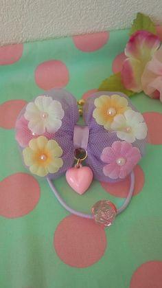 ●お花を閉じ込めたリボンです。オーガンジーの上にお花をのせ、さらにチュールを重ねていますので、ふんわりですが、しっかりしたお作りになっているかと思います。●お花の真ん中には、パール風パーツをつけ、リボンのセンターにハートをぷらぷらさせました。お色は、パー...