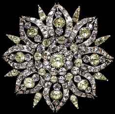 Made between 1700 and 1800, this brooch in the shape of an eight-petal flower is comprised of light yellow chrysoberyls and delicate pink topazes set in silver.  The stones were mined in Brazil for export to Britain.