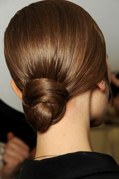 She has a small hairnet holding her hair in the bun. If you have grey hair there is no need---just spray it.