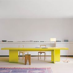 neon yellow dining table in an all white, sleek kitchen