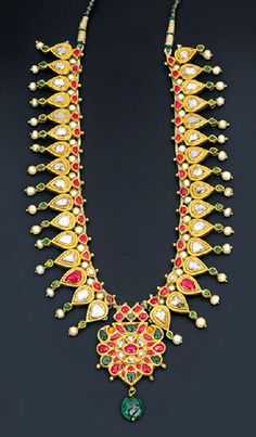 AN ATTRACTIVE DIAMOND AND GEM-SET PENDENT NECKLACE   Centering upon a ruby, emerald and diamond-set foliate cluster pendant suspending an emerald bead from a series of inverted pear-shaped panels set with table-cut diamonds with gem-set detail to the seed pearl fringe, South Indian, mid 19th century, 35.0cm long