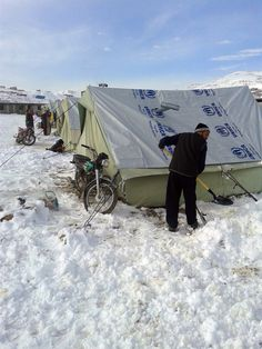 A Syrian refugee shovels snow following a storm in the town of Arsal in the Lebanese Bekaa valley on December 12, 2013. The UNHCR has prepared stockpiles of items including plastic sheeting, floor mats, blankets and mattresses to help refugees whose shelters might be flooded or destroyed by the storm.