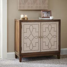 Crafted from hardwood solids, veneers and fabric door fronts, this two tone nailhead chest features one adjustable shelf behind its two doors.