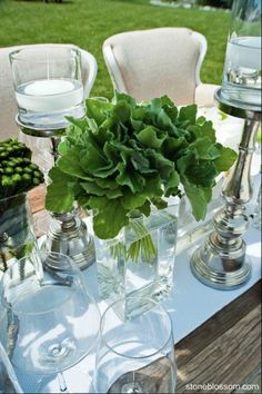 Simple leaves on a rustic farm table with upholstered chairs surrounded by candelight