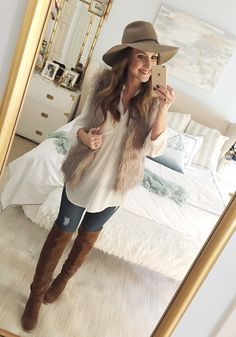Blogger Mallory Fitzsimmons of Style Your Senses wears an ivory tunic, faux fur vest, skinny jeans and over the knee boots for a festive Thanksgiving outfit idea
