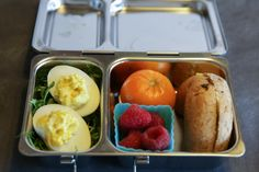 PlanetBox Shuttle packed with deviled eggs over greens, a clementine, raspberries and 1/2 a sprouted wheat bagel.