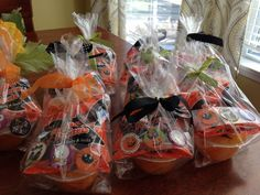 """Halloween gift bags for 2 year olds. Mandarin orange cups with jack o lantern faces drawn on, mini halloween shaped pretzels, and halloween stickers in a cello bag with small ribbon. Washi tape """"happy halloween from..."""" Message on the back. Super cute and inexpensive!"""