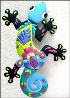 "Blue & Black Gecko Painted Metal Wall Décor - 16"" x 24"" . $39.95. Hand painted metal gecko wall hanging. Can be used both indoors and outdoors. The gecko is hand cut from recycled steel drum. The details of the design have been hammered into a bas-relief to accent the painted decorative designs. The choice of rich colors is especially attractive. The painting style is similar to that found on Spanish & Mexican talavera pottery."