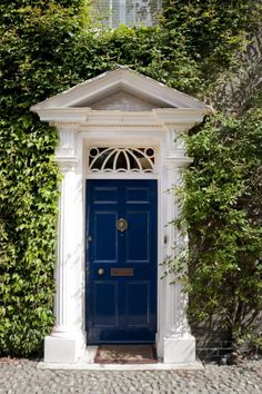 This doorway's stately columns and intricate fanlight only add to the grandeur that the vines offer this home.