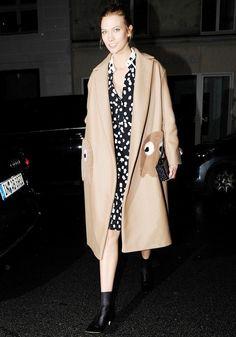 Karlie Kloss wears a polka dot printed dress, Anya Hindmarch oversized coat, and black booties.
