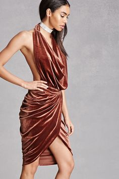 A velvet dress featuring a backless design, halter neckline, cowl front, ruched sides, and a tulip hem.  This is an independent brand and not a Forever 21 branded item.