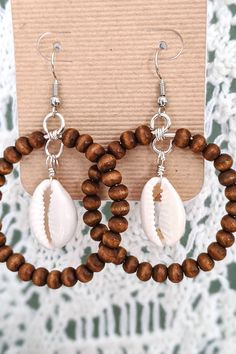 Wooden beaded hoop with Cowrie Shell accent, made with silver-colored wire. These handmade statement earrings are perfect Bohemian Inspiration! Handmade Wire Jewelry, Seashell Jewelry, Handmade Jewelry Designs, Earrings Handmade, Handmade Accessories, Shell Earrings, Beaded Earrings, Statement Earrings, Drop Earrings