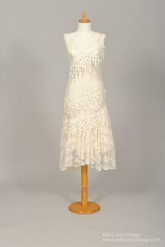 Conçu dans les années 70, cette robe de mariée vintage fabuleux est réalisée dans une fine dentelle brodée net avec suspension libre appliqués tout au long de. Nous avons montré cette robe avec un glissement, pas inclus, mais fortement recommandé. Le corsage sans manches vous offre un décolleté ornée de bijoux. Les appliques sont appliquées en diagonale et la jupe de cette robe colonne est faite en deux niveaux ourlet asymétrique. 11 boutons nacrés joindre cette robe dans le dos. Nous…