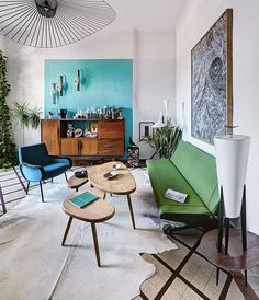 The Marseille apartment of vintage furniture restorers Virginie and Jean-Baptiste Moutte. I really like the turquoise feature wall, and the fact that it does not go up to the ceiling but is limited to that area. The ceramics pop against it. I also enjoy the colourful furniture such as the blue chair and green sofa. The ceiling light is wonderful and the black on white painting pairs beautifully with it.