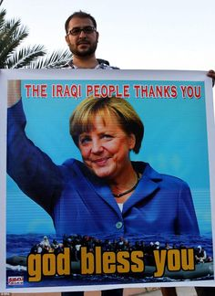 An Iraqi holds a picture of the German Chancelor, Angel Merkel (pictured), during a demons...