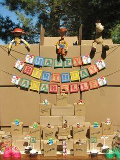 Mesa de postres de Fiesta Toy Story decorada con cajas, super ingenioso.