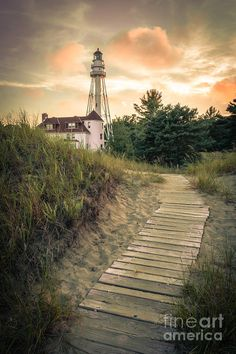 Rawley Point Lighthouse Under Smoldering Skies by Mark David Zahn Photography. The Rawley Point Lighthouse, a historical fixture overlooking the sandy shores of Lake Michigan, stands tall against the golden red skies of dusk. The lighthouse, a popular spot at Point Beach State Park in Two Rivers, Wisconsin, finds itself alone on this late summer evening.