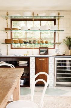 Open glass shelving with brass accents in front of large wooden framed kitchen window, and patterned tile.