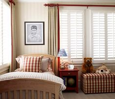 """Tone-on-tone striped walls and a maple bed stay quietly in the background while red accents (such as the drapery hardware) add energy and life to this bedroom built for a boy. Red-plaid fabric turns an upholstered storage ottoman and decorative pillow into points of interest.  This bedroom will seamlessly adapt with age. A solid red side table displays a baseball lamp and globe that say """"boy"""" but can just as easily hold a smart phone and tablet for a teen in a few years."""