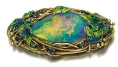 Gold, enamel and opal brooch, Louis Comfort Tiffany, Circa 1910 - Sotheby's  Centring on a black opal within a textured surround of fruiting vine leaves decorated with blue and green enamel, accented with circular-cut sapphires and green garnets, signed Tiffany & Co. Estimate: 4,000 - 6,000 GBP