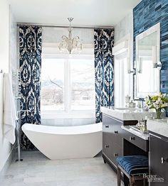 Blue universally pleases due to its familiar associations with sea and sky, its calming properties, and its versatility. A deep blue backsplash showcases a clean, modern tub. The hue repeats in a window treatment that visually expands the space while highlighting silver finishes found in the bathroom's chandelier and vanity.