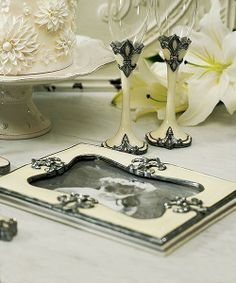 Fleur De Lis Wedding Guest Book features a poly resin cover in an antique ivory color.  Four Fleur de Lis decorate the front cover, painted in an antique silver finish. It also has a picture window for you to add your favorite photo.