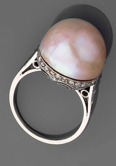 A cultured pearl, diamond and platinum ring, circa 1930. Centring a pink mabé pearl, mounted in a pierced platinum gallery set with rose-cut diamonds. #ArtDeco #ring