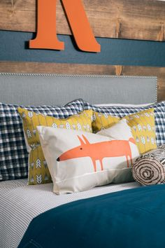 Wood boards stripe the navy wall behind an upholstered gray headboard with nailhead trim. Blue, gray and white plaid pillows, yellow arrow patterned pillows, a fox pillow and a wood patterned round lumbar pillow create a cushioned and colorful bed setup to brighten the navy comforter.